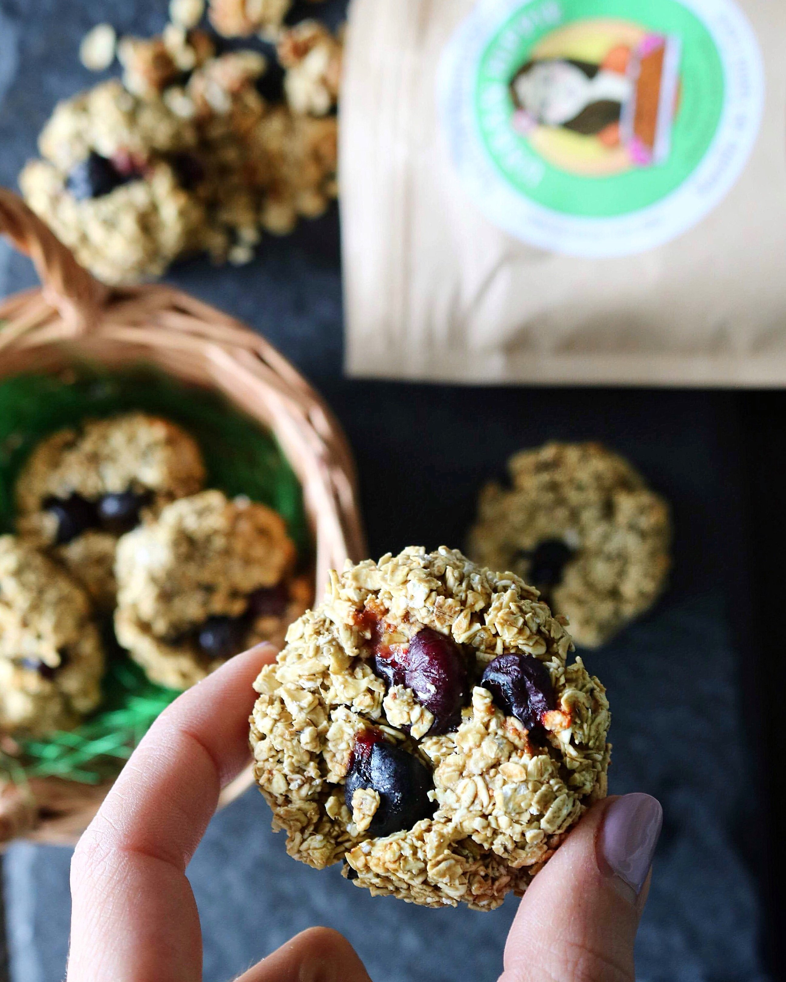Holding between two fingers a vegan granola cookie with a bag of Urban Hippie Granola peeking out from the side of the image